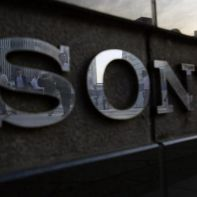 Pedestrians are reflected in a logo of Sony Corp outside its showroom in Tokyo July 16, 2014. REUTERS/Yuya Shino